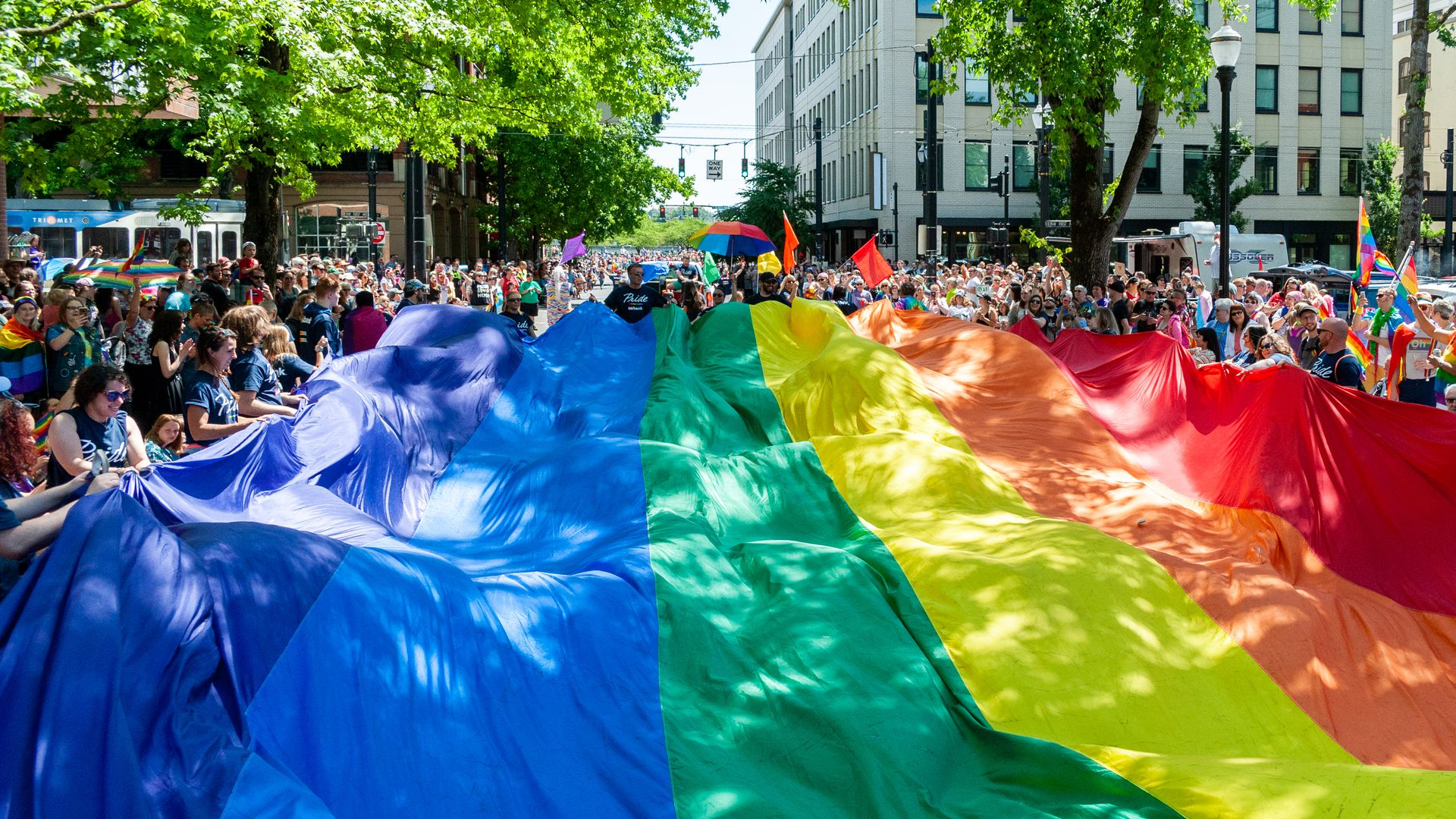 This image shows a large Pride flag being carried down a street.