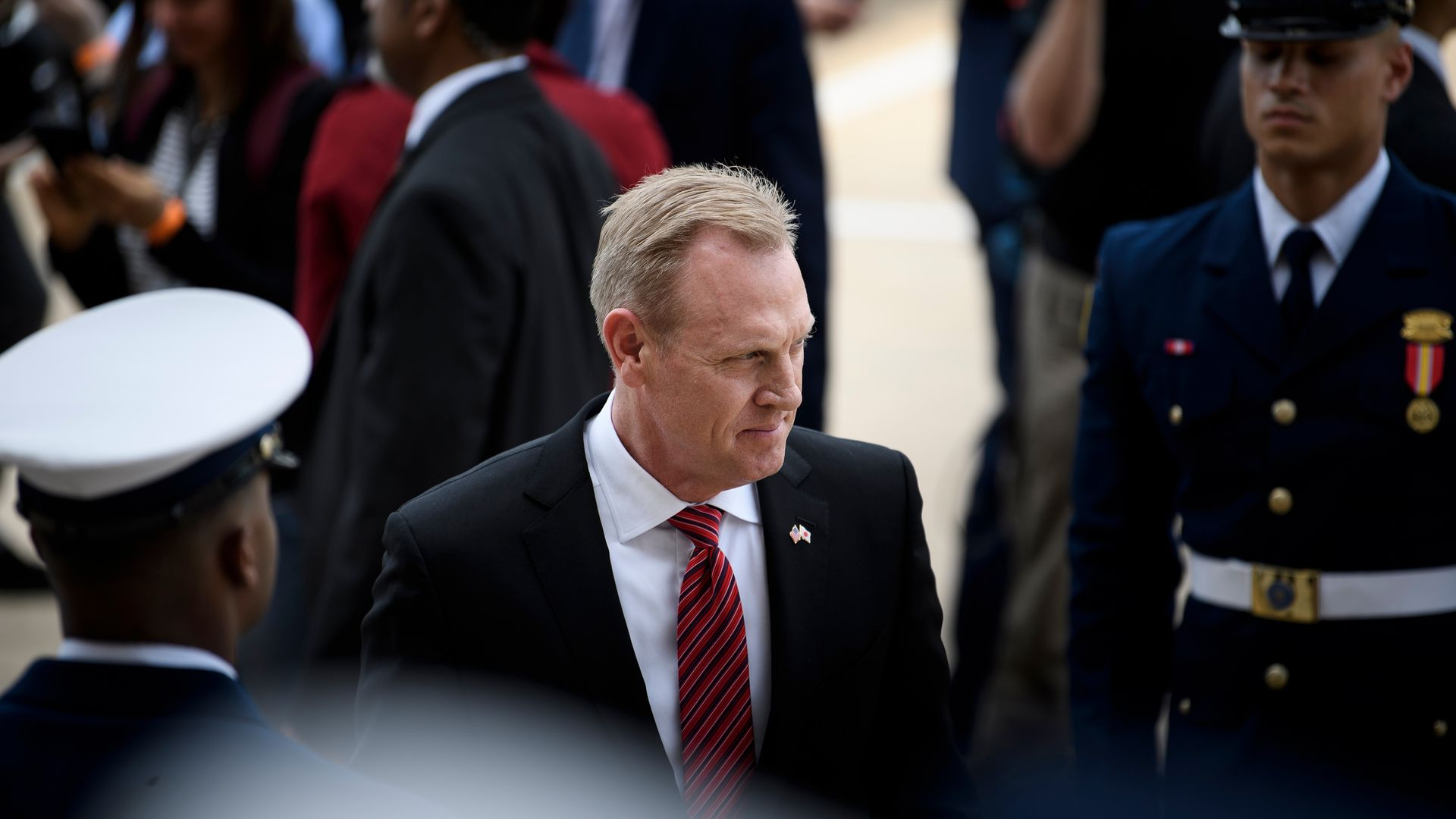 Acting Defense secretary Patrick Shanahan walks past troops in uniform.