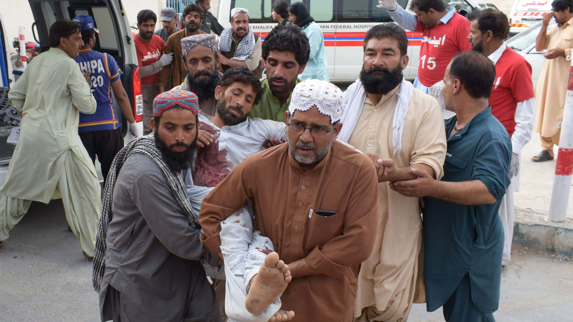 An injured Pakistani man is carried to a hospital