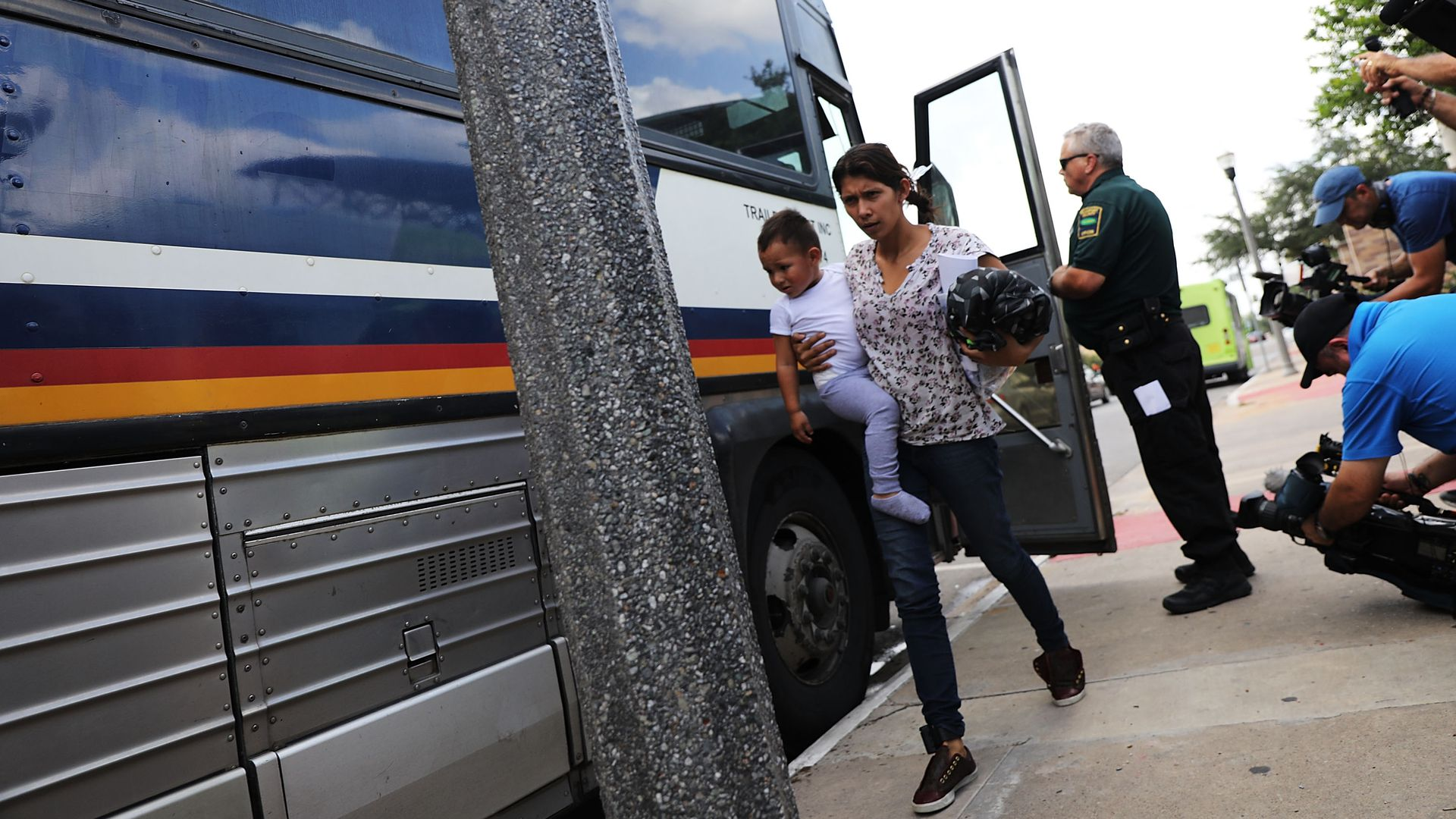 A migrant woman and her child get off a bus