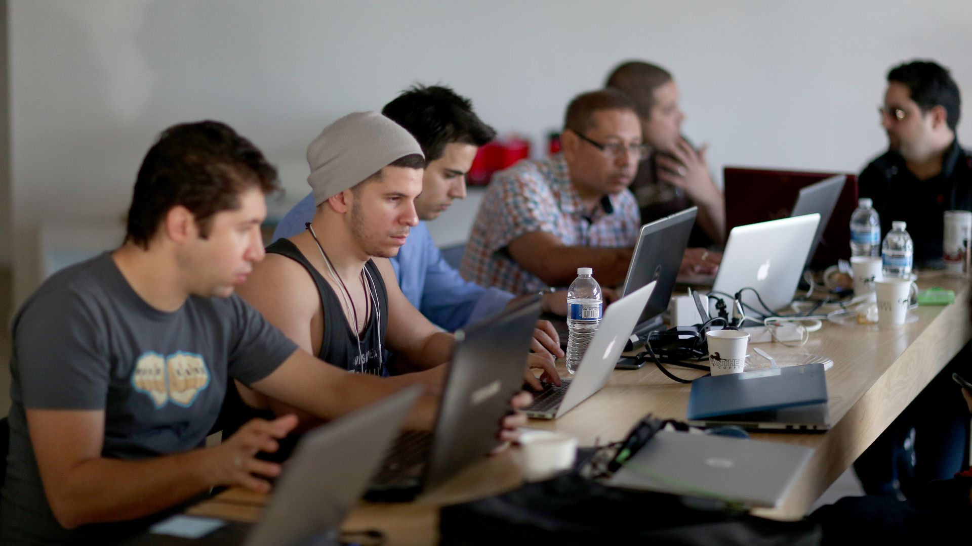 computer programmers working on laptops at a table