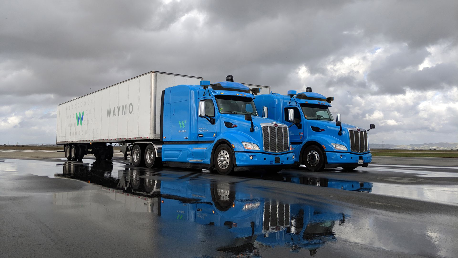 image of 2 commercial trucks operated by Waymo's self-driving technology