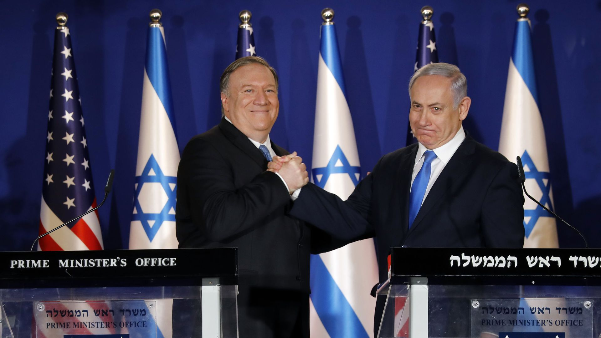 Mike Pompeo and the Israeli prime minister shake hands in front of a row of Israel and American flags, standing behind two podiums.