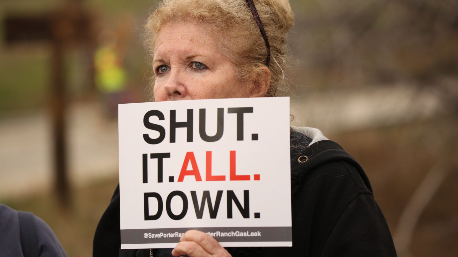 Local resident Maureen Capra holds sign as she listens to Rep. Brad Sherman, D-Sherman Oaks,