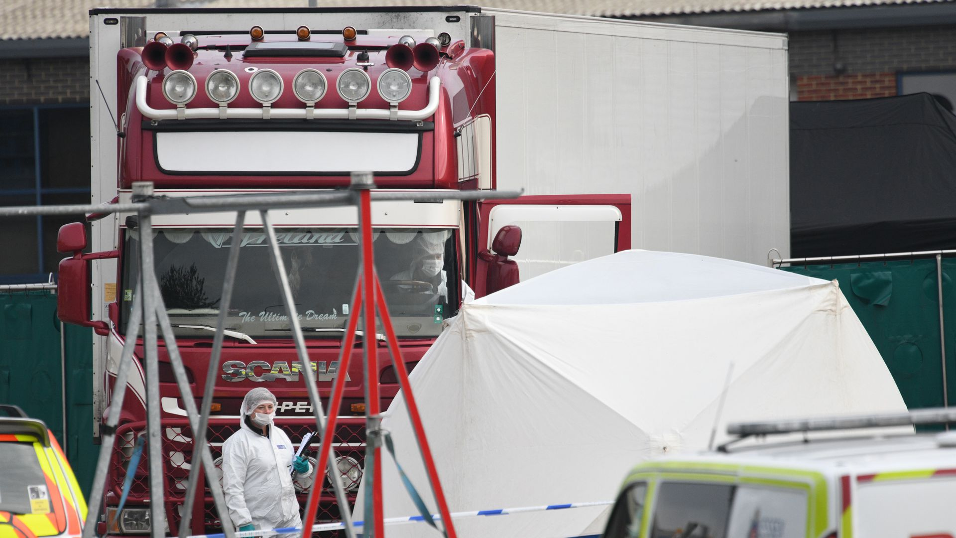 Forensic officers stand in front of the truck in which 39 bodies were discovered.