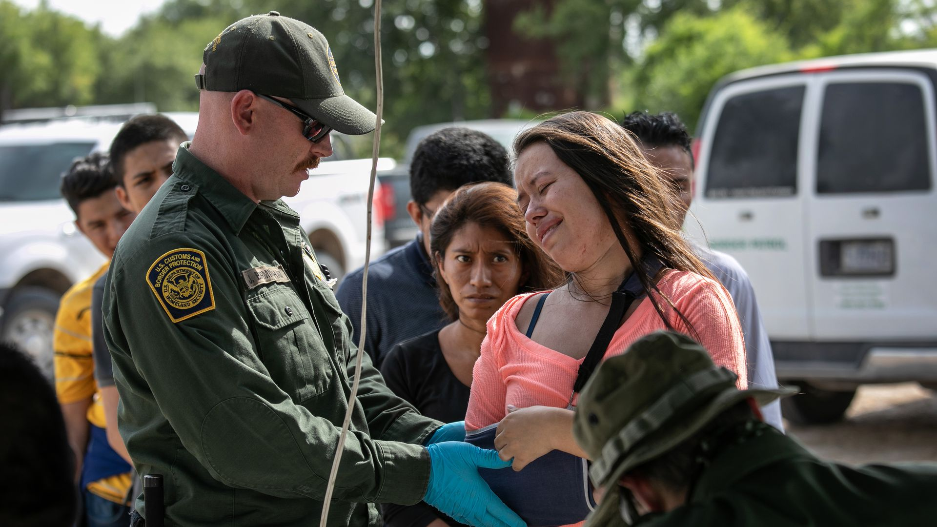 A border patrol officer checks a migrant's arm which is in a cast.