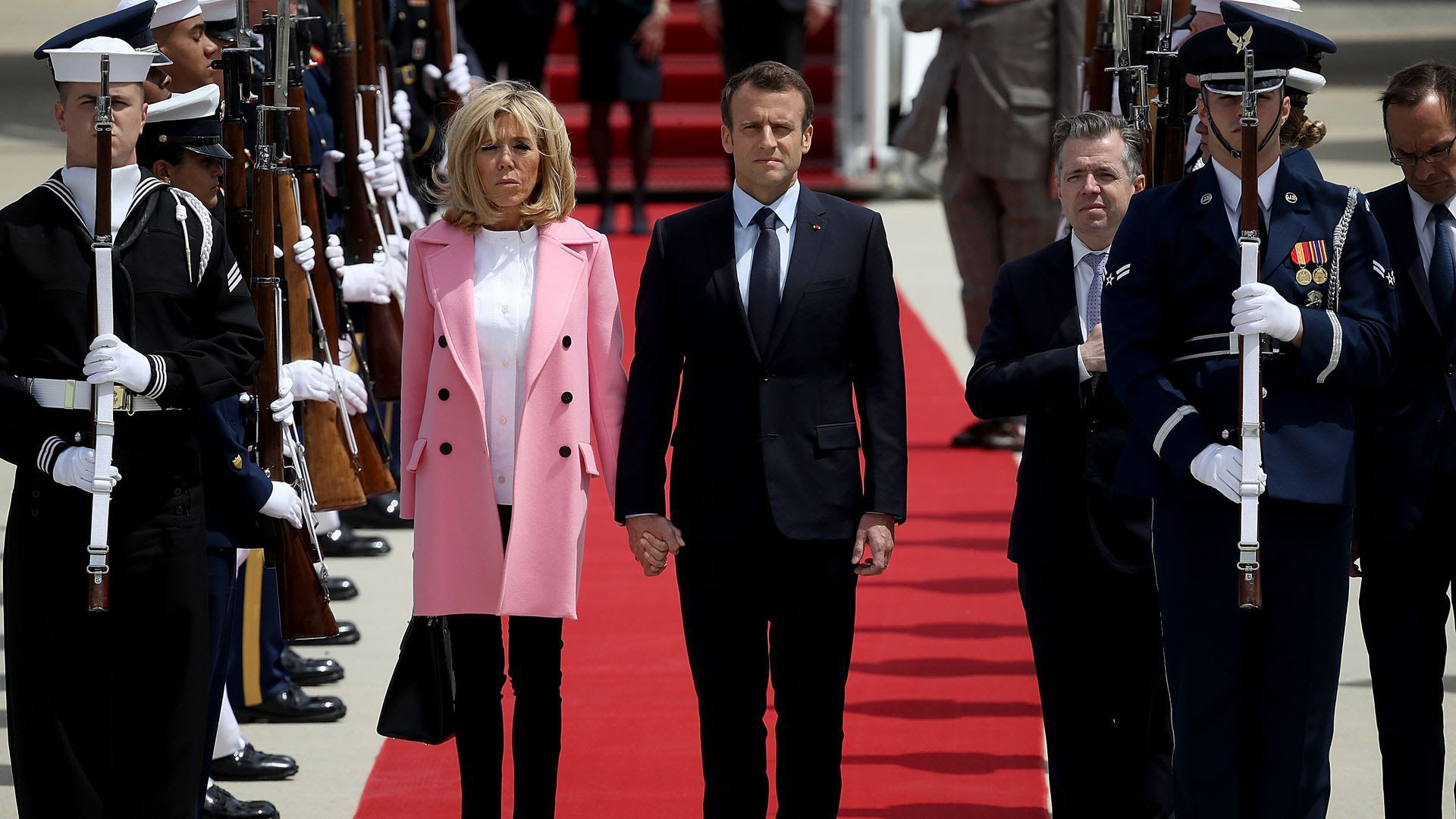 French President Emmanuel Macron and his wife Brigitte stand side by side after deplaning
