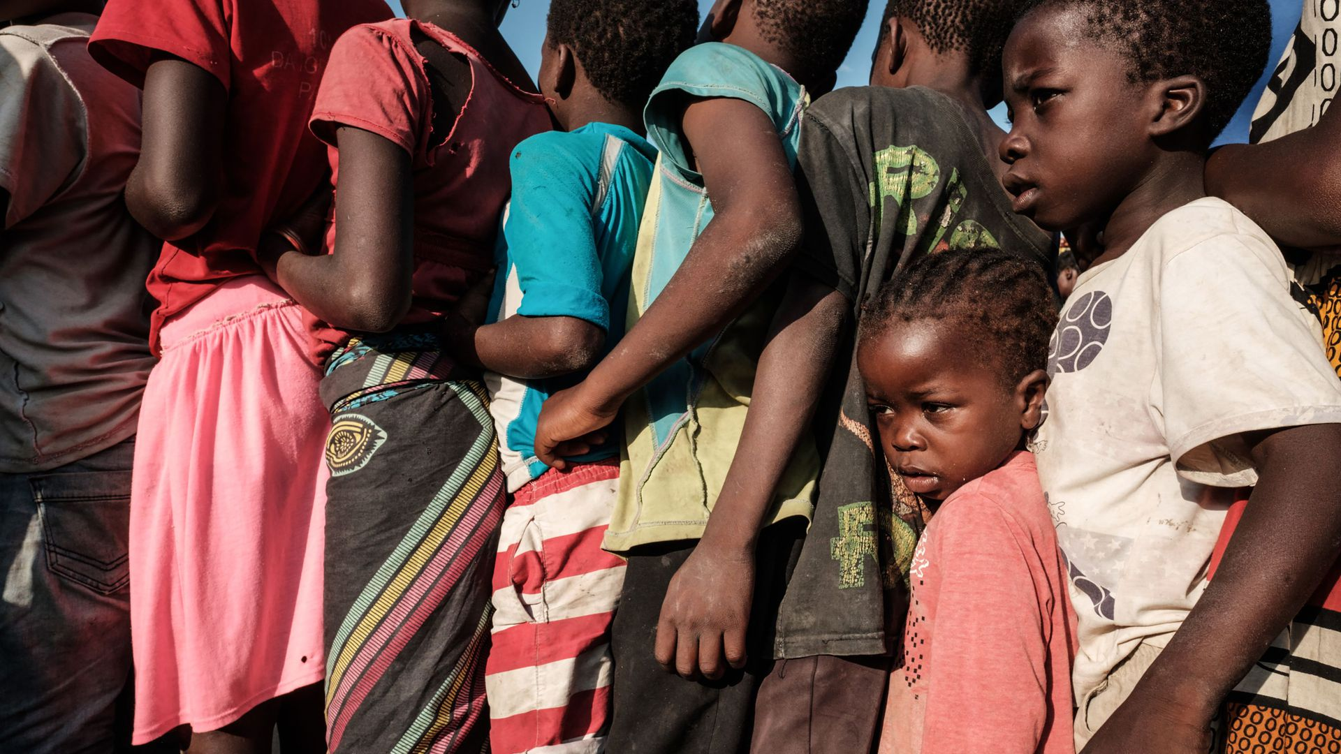 Children in Mozambique wait in line for food following Cyclone Idai