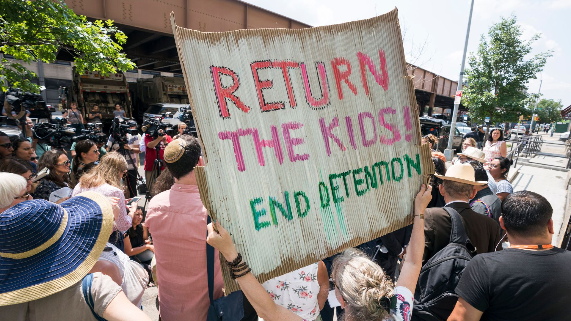 "A protestor holding a sign that says ""return the kids, end detention"""