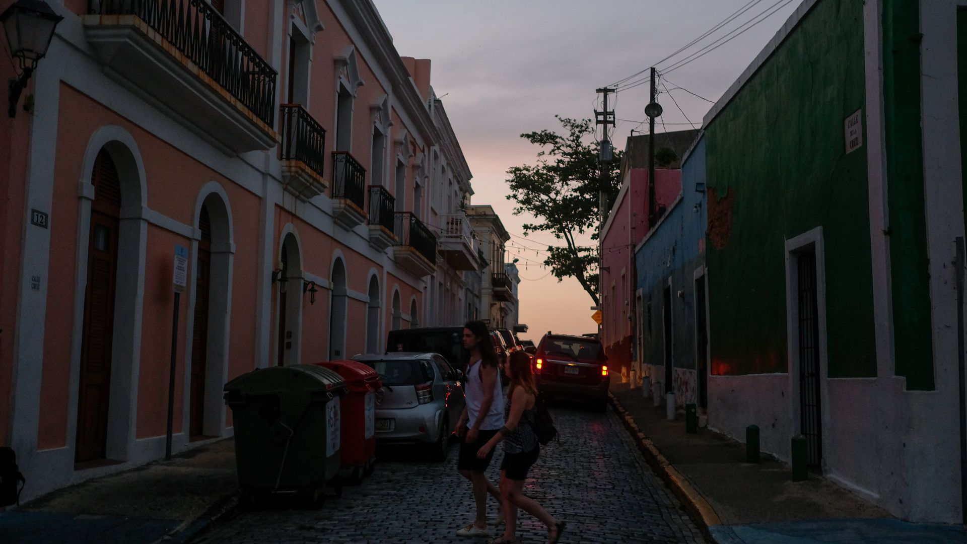 Tourists walk along a street with no electricity.