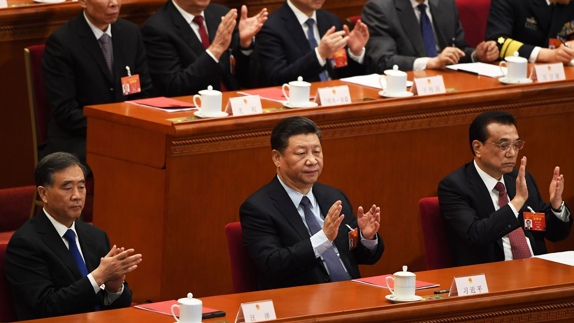 President Xi Jinping and other Chinese officials applaud at the National People's Congress.