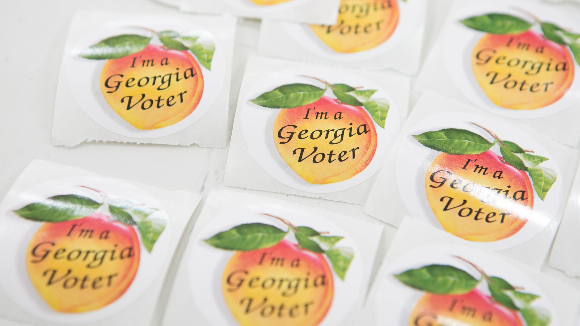 "Stickers of a peach, saying ""I'm a Georgia voter"""