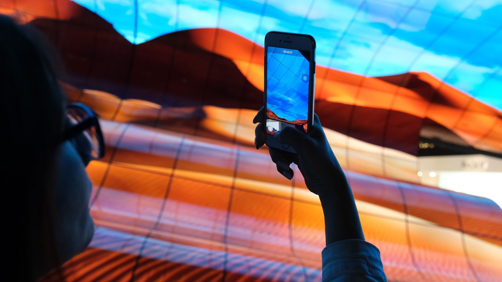 A visitor photographs a display of curved OLED TVs at the LG stand at the 2019 IFA home electronics and appliances trade fair. Photo: Sean Gallup/Getty Images