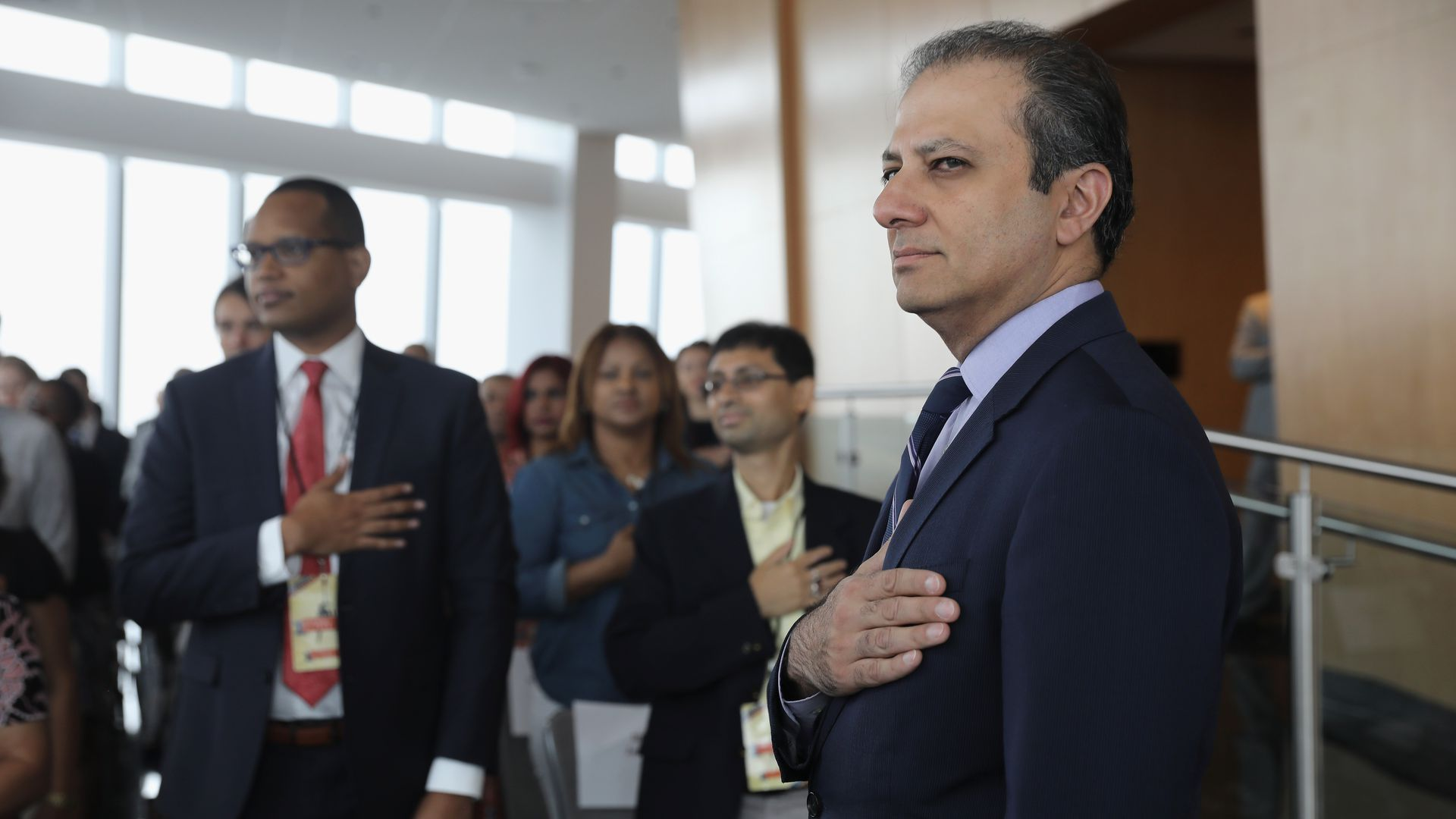 Preet Bharara stands with his hand over his heart.