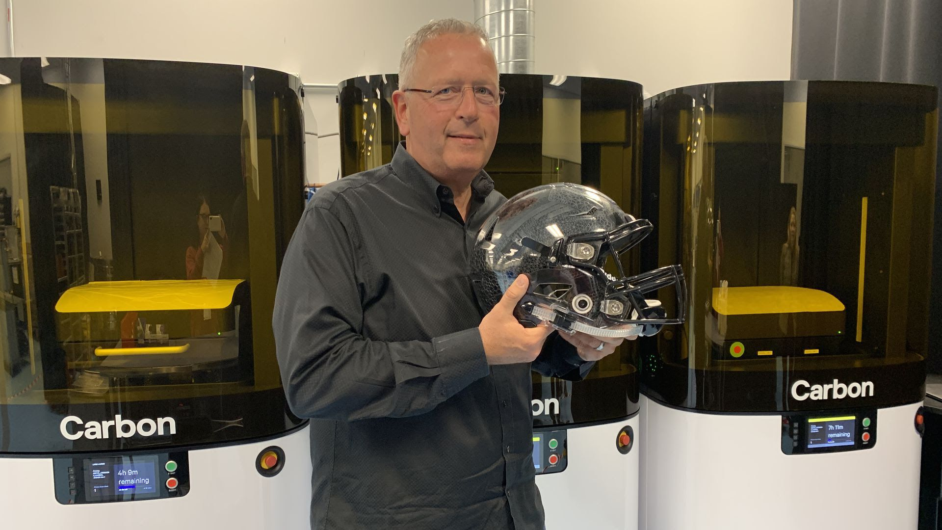 Carbon CEO Joe DeSimone holding a football helmet with 3D printed inserts using the new L1 printer.