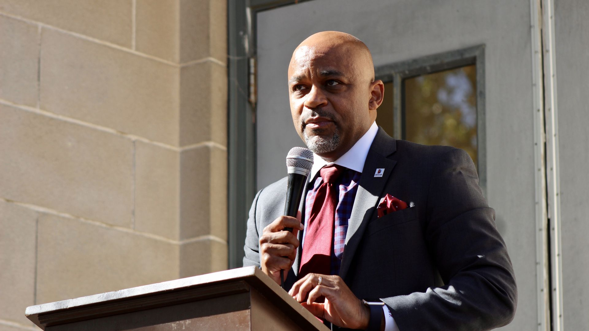 A photo of Mayor Michael Hancock outside standing behind a podium and holding a microphone
