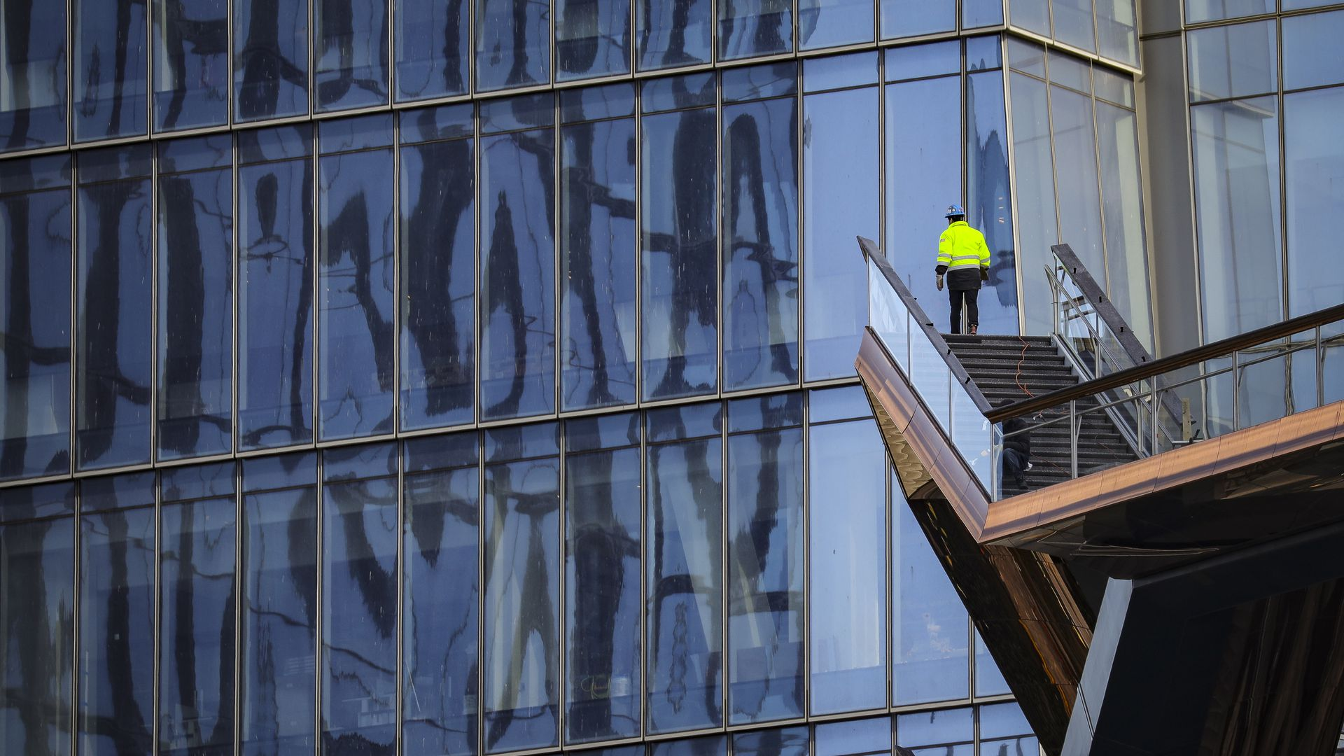 A construction worker stands at the end of a ladder in front of a New York skyscraper.