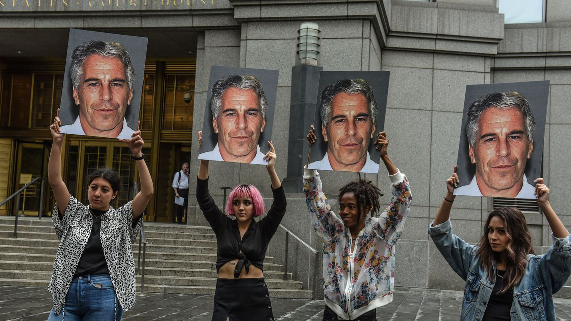 Protesters hold placards of convicted sex offender Jeffrey Epstein.