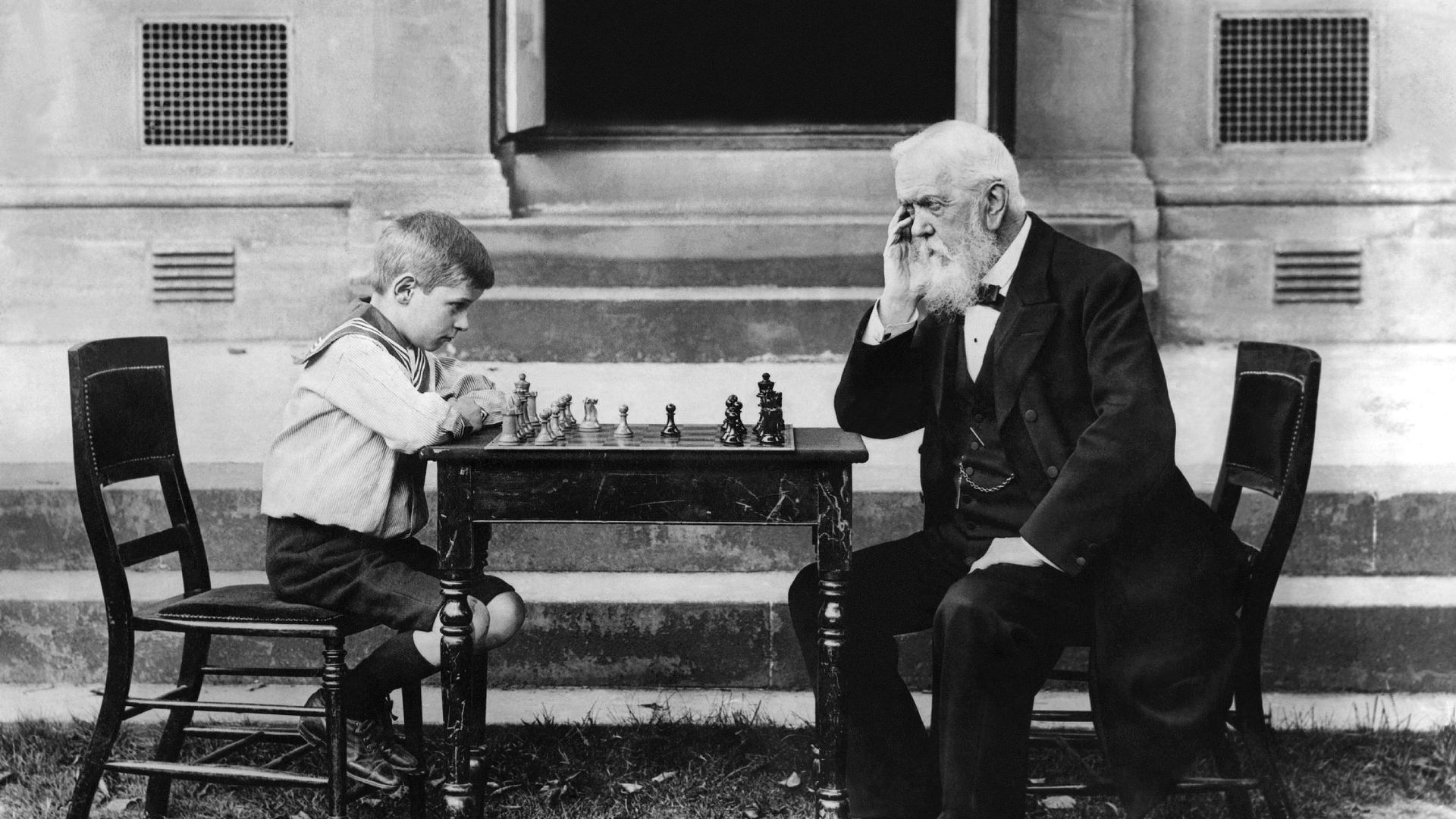 Young boy playing a game of chess with an old man.