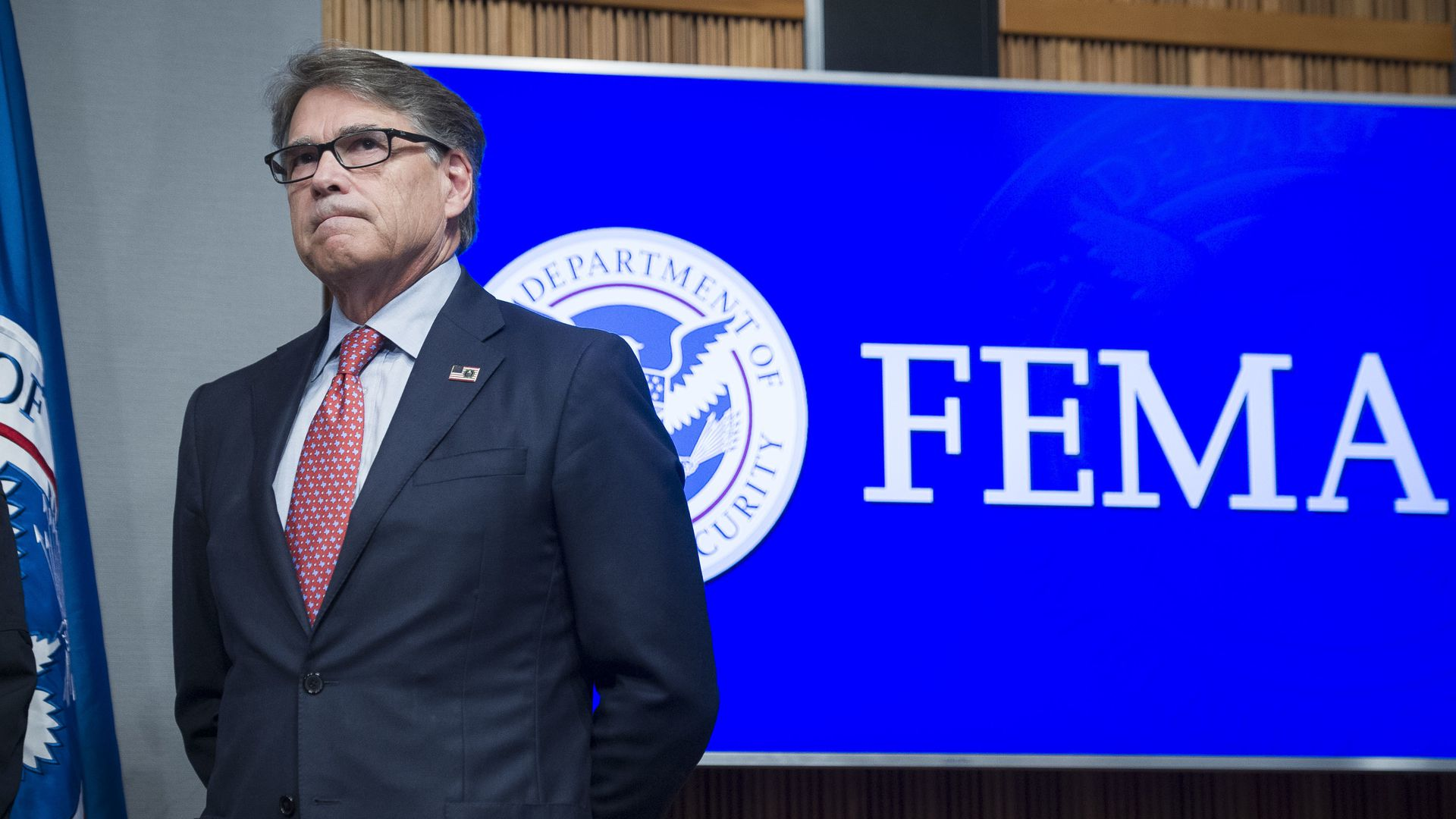 Energy Secretary Rick Perry stands with his hands behind his back in front of a blue FEMA sign.