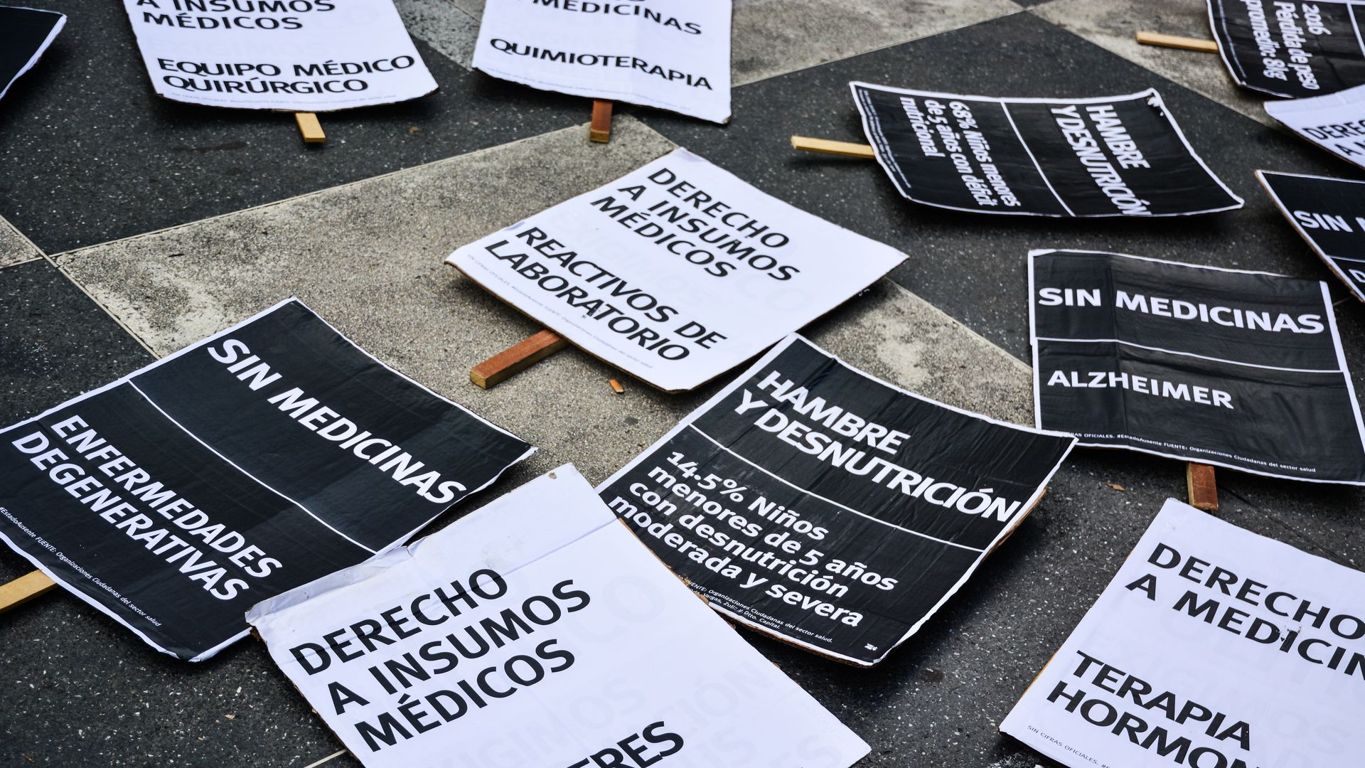 Protest signs in Caracas, Venezuela, where a drug shortage has exacerbated a malaria outbreak.