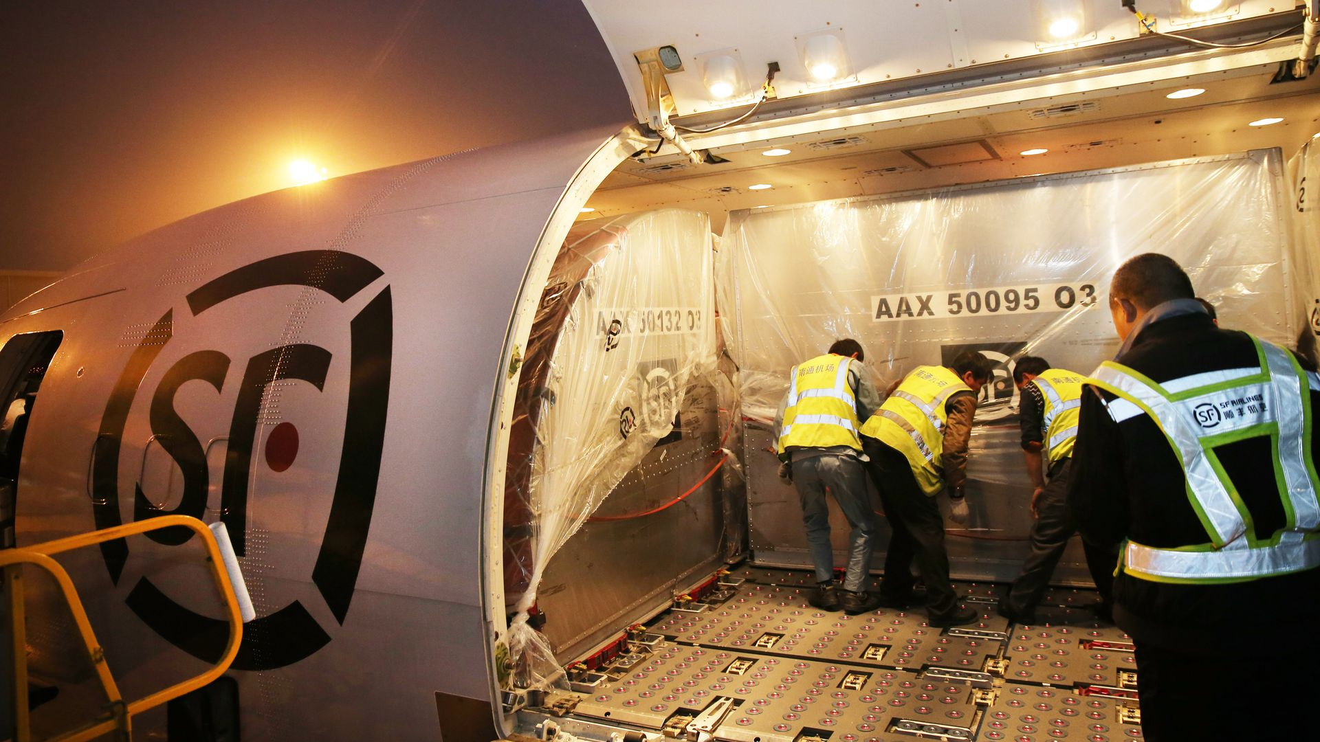 Crews help load parcels for delivery on SF airlines