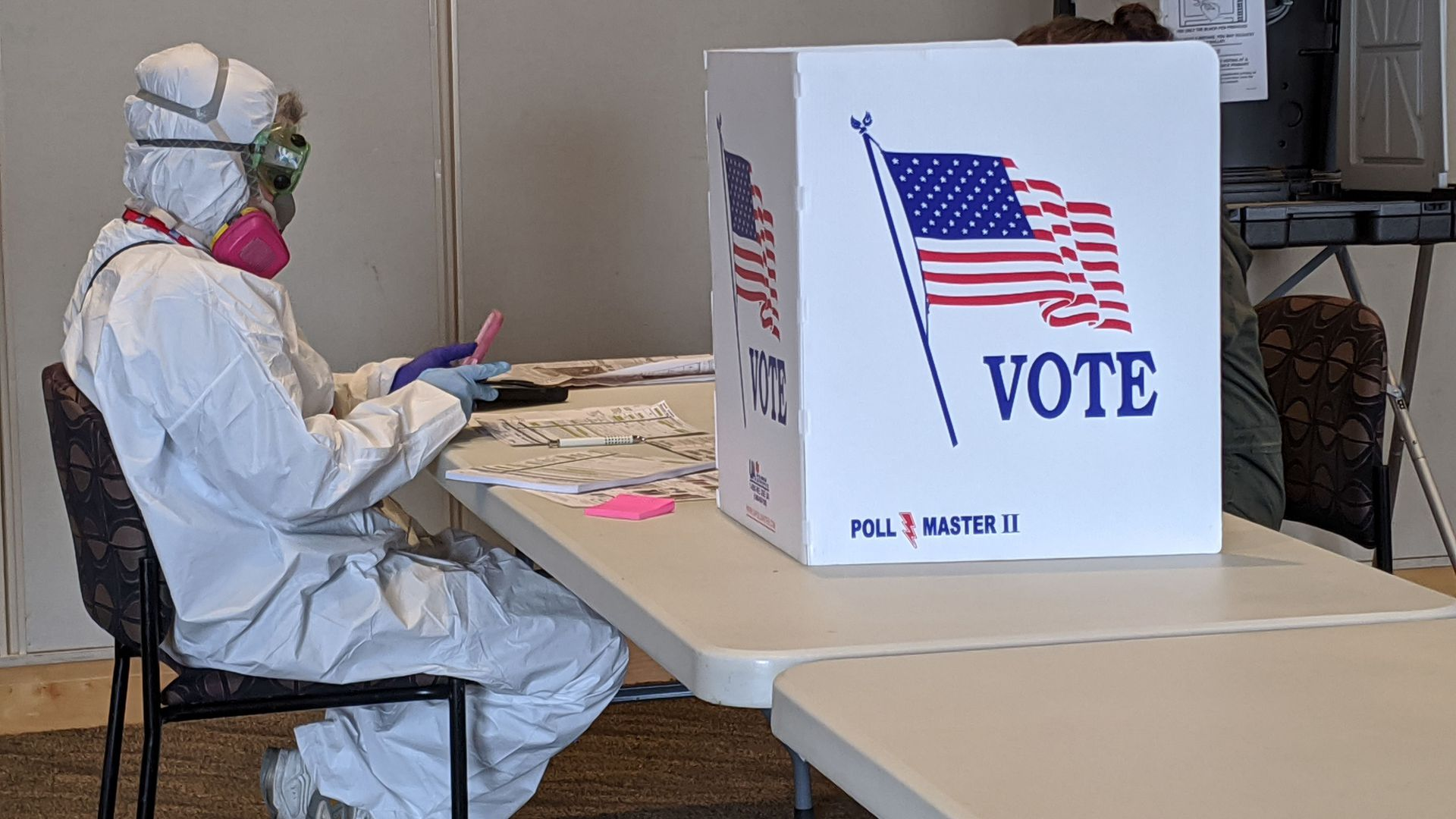 In this image, a person in a hazmat suit and gas mask sits in front of a voting booth