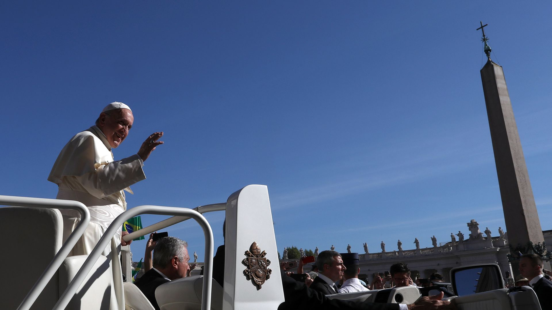 Pope Francis waving to a crowd.