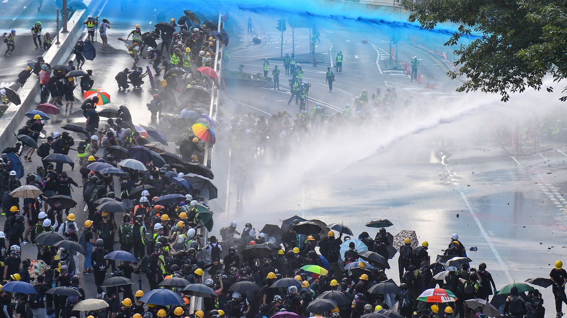 Pro-democracy protesters react as police fire water cannons outside the government headquarters in Hong Kong on September 15