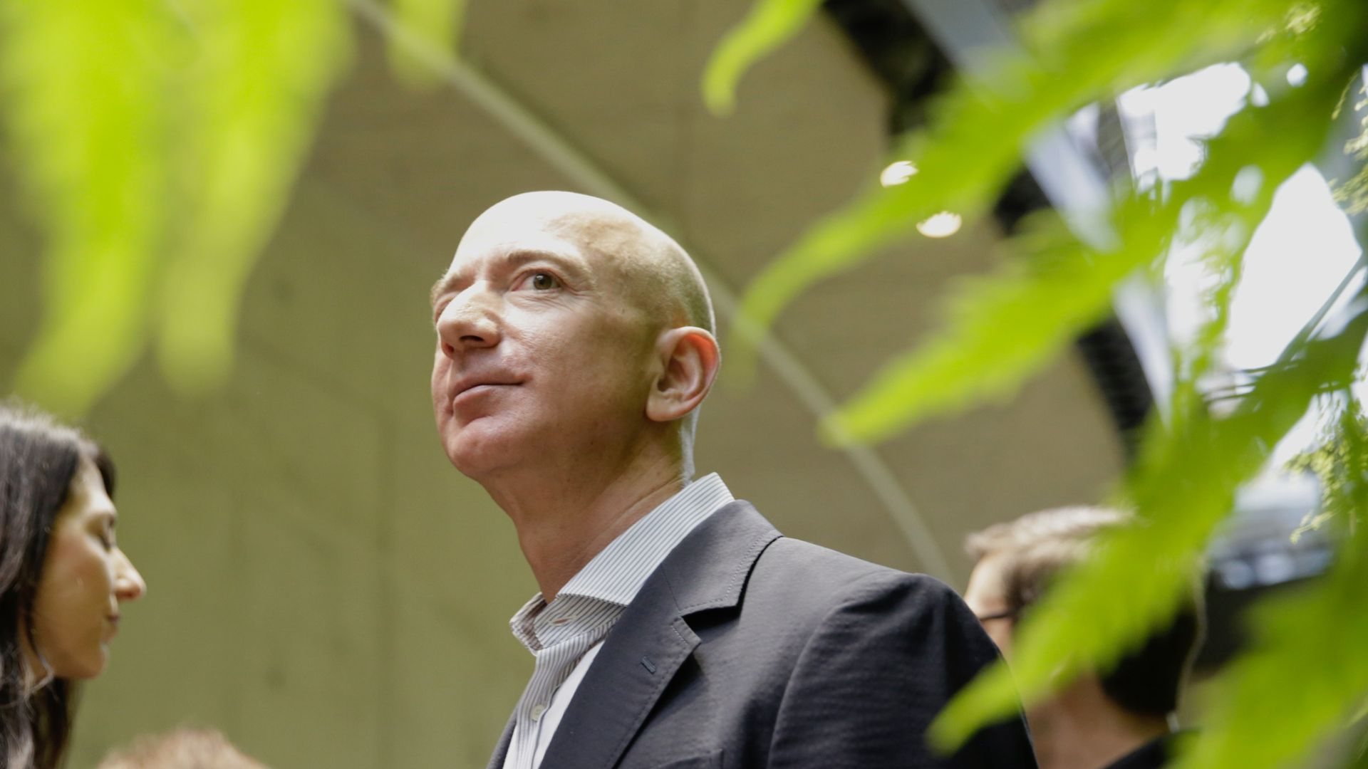 Jeff Bezos in focus in the background, with a green plant, out of focus, framing him in the foreground