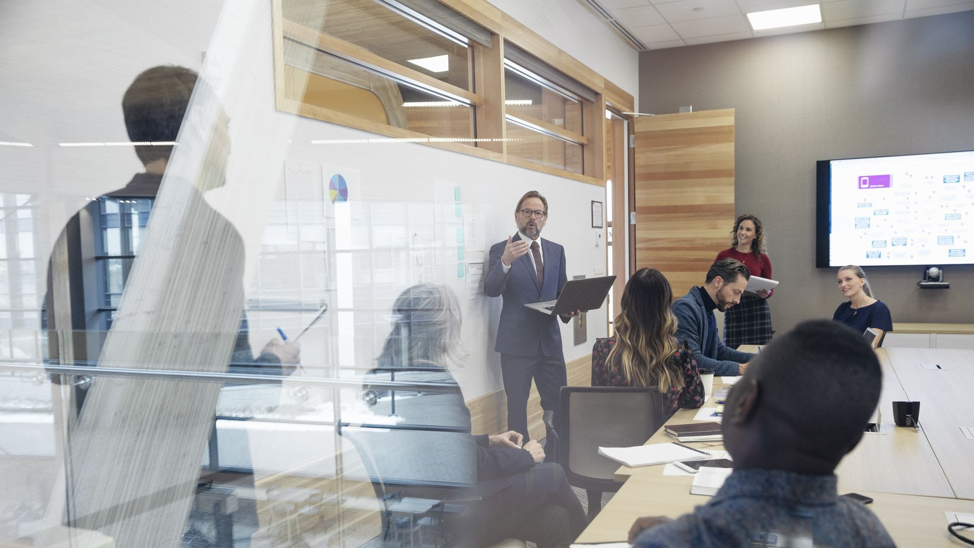 A man giving a presentation to people at his company