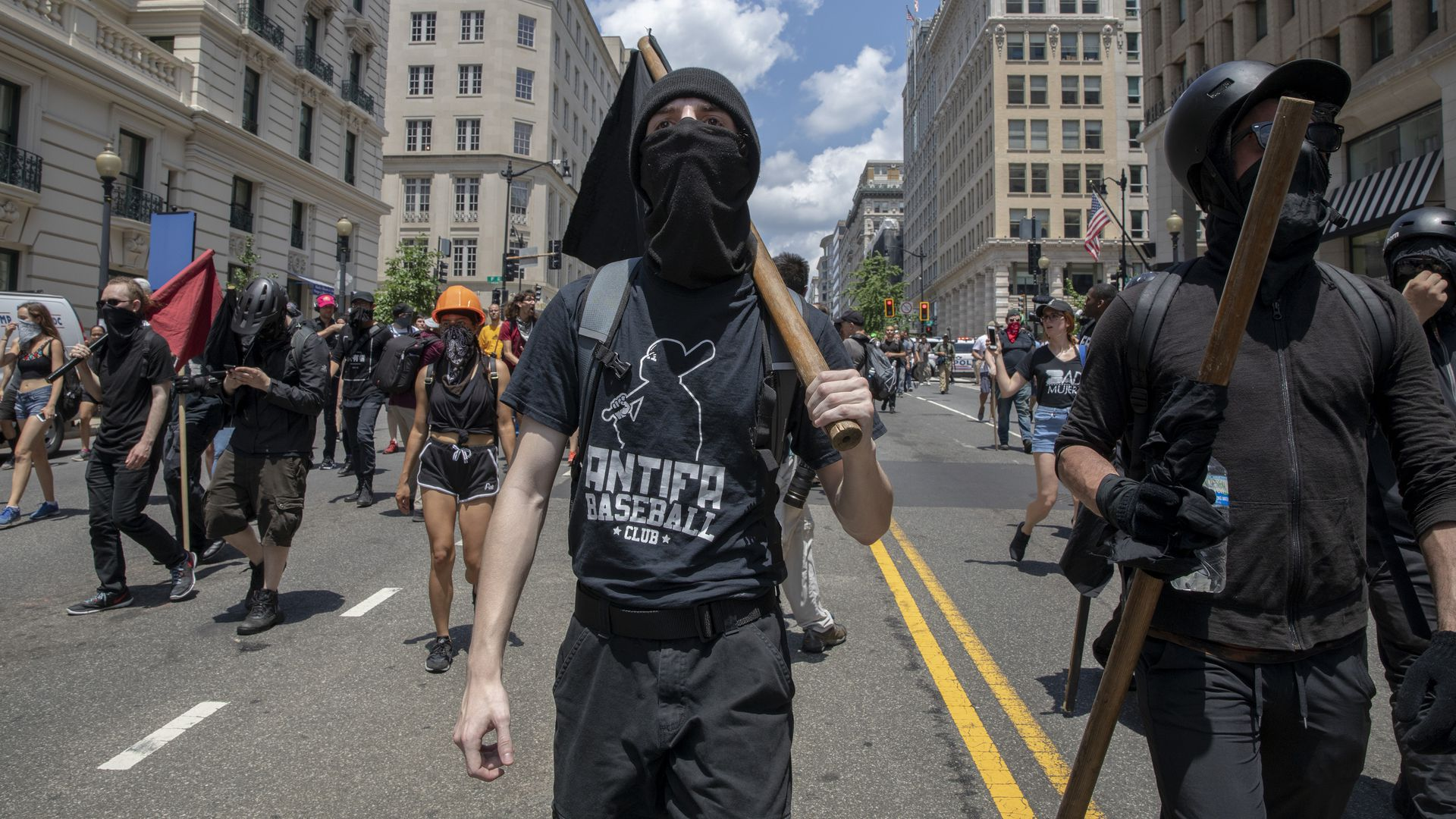 This image shows two black-clad antifa members carrying black flags down the street with their faces covered. other members follow behind them.