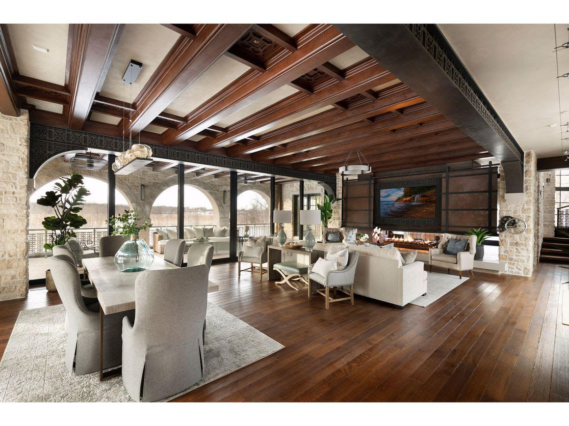 The interior of a living room inside a $7.5 million mansion for sale in Orono, Minnesota, with large floor-to-ceiling windows and a white couch.