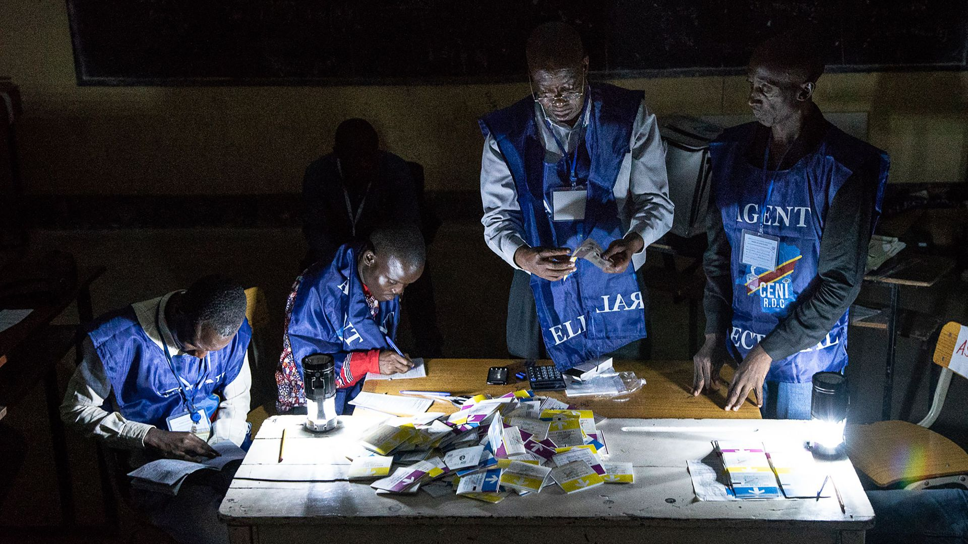 Independent National Electoral Commission (CENI) agents count votes during an electricity cut while watched by observers at Kiwele college in the Democratic Republic of Congo.