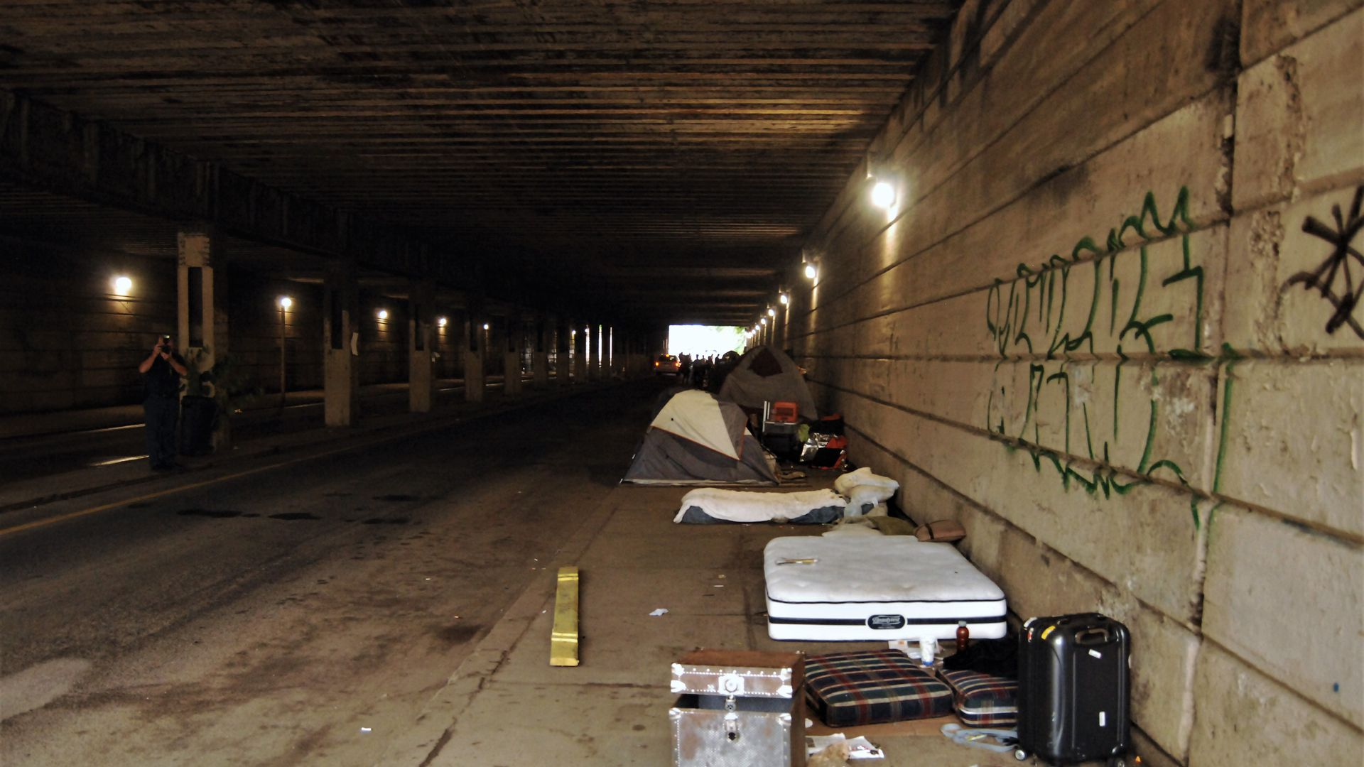 Makeshift beds for homeless people under a highway