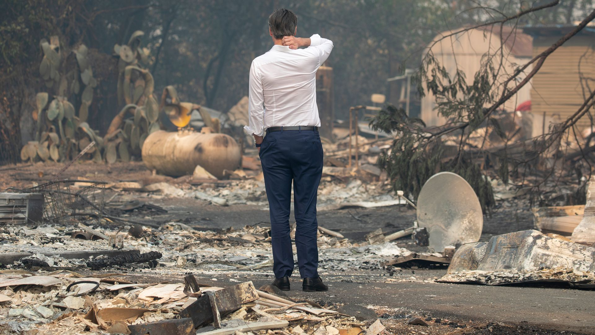 In this image, Gavin Newsom stands in a dress shirt and slacks in the middle of a rubble-filled, burned-out street after a large fire