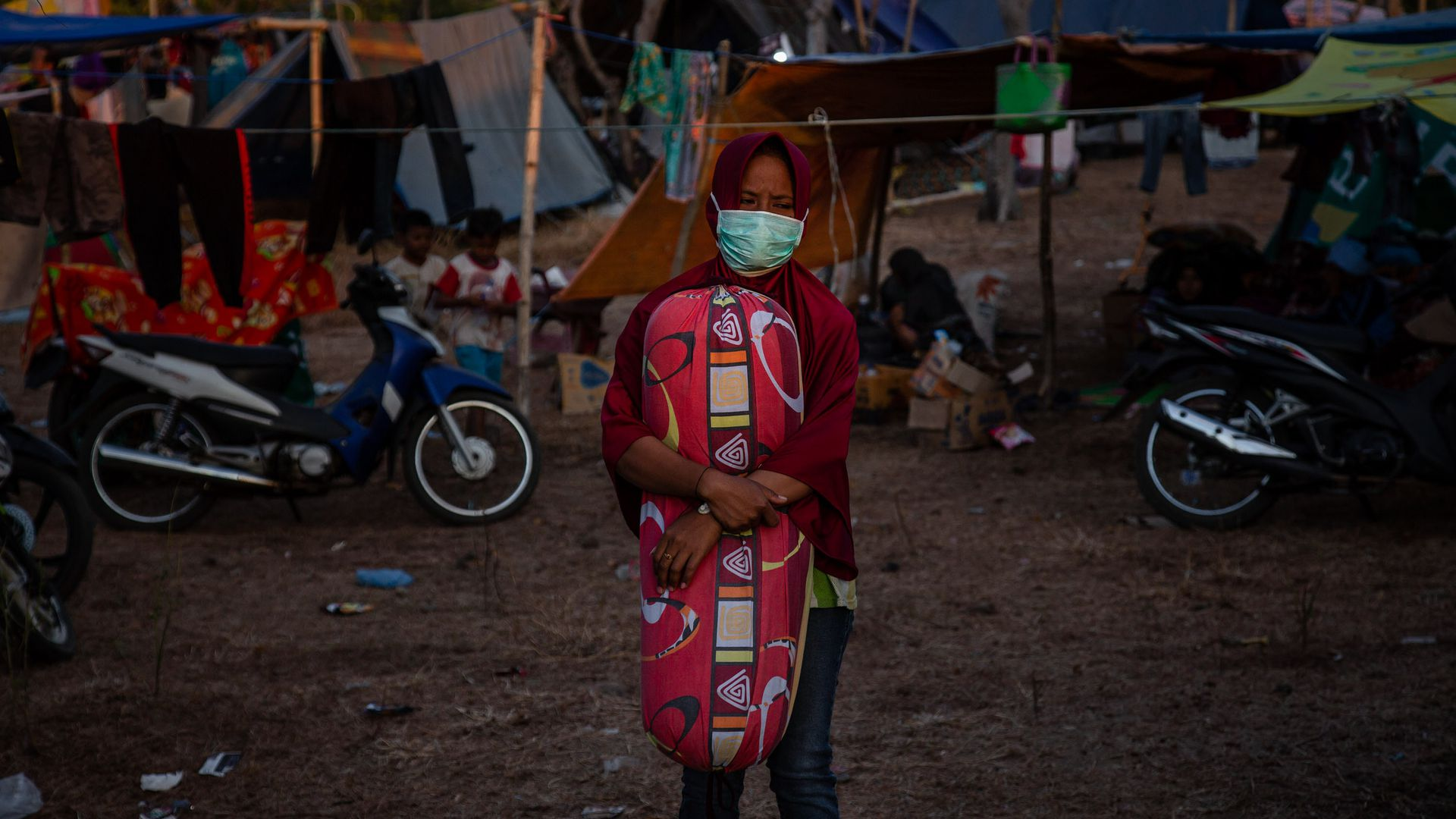 A girl standing in a temporary shelter.