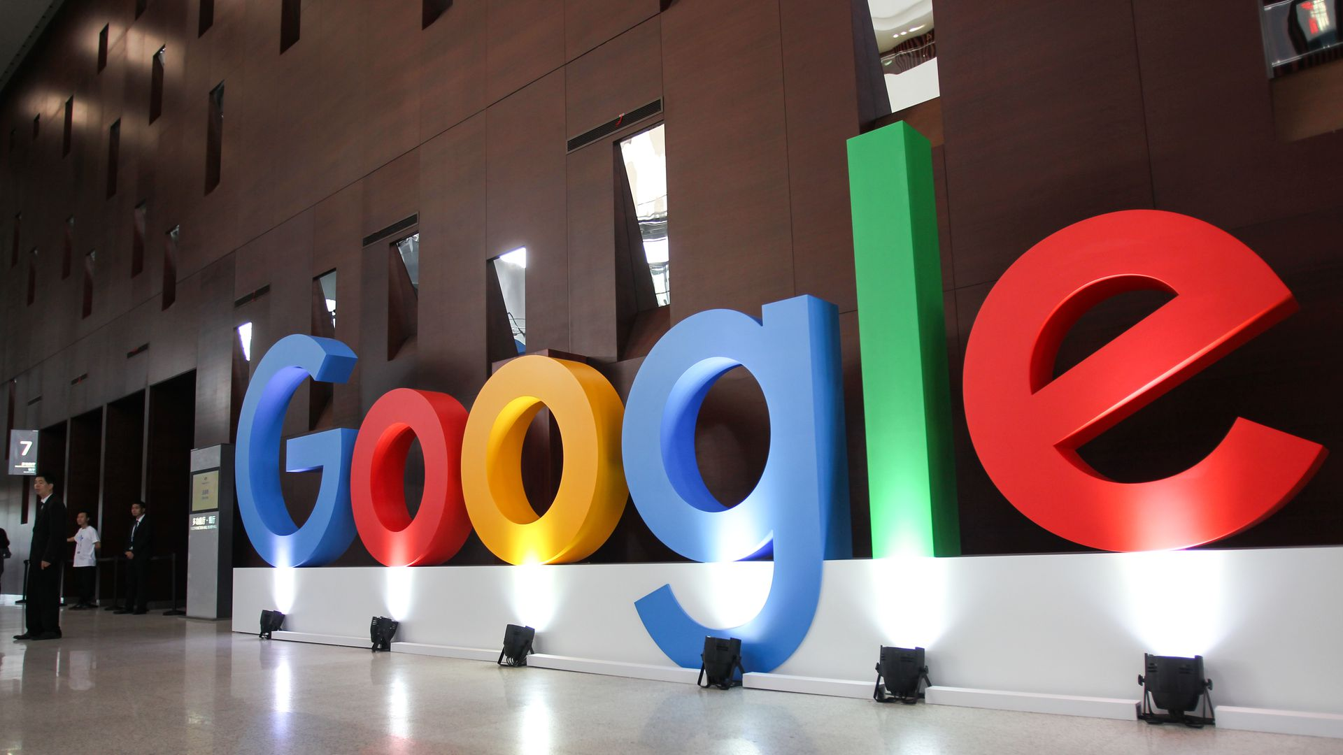Google's multi-color logo with lights shining underneath it.