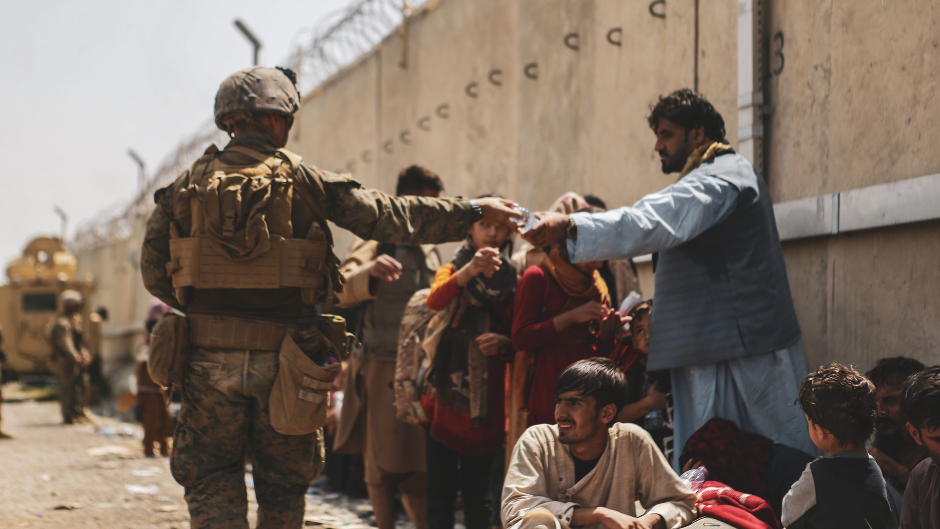 A U.S.  Marine passes out water to evacuees during the evacuation at Hamid Karzai International Airport. Photo: Isaiah Campbell/U.S. Marine Corps via Getty Images