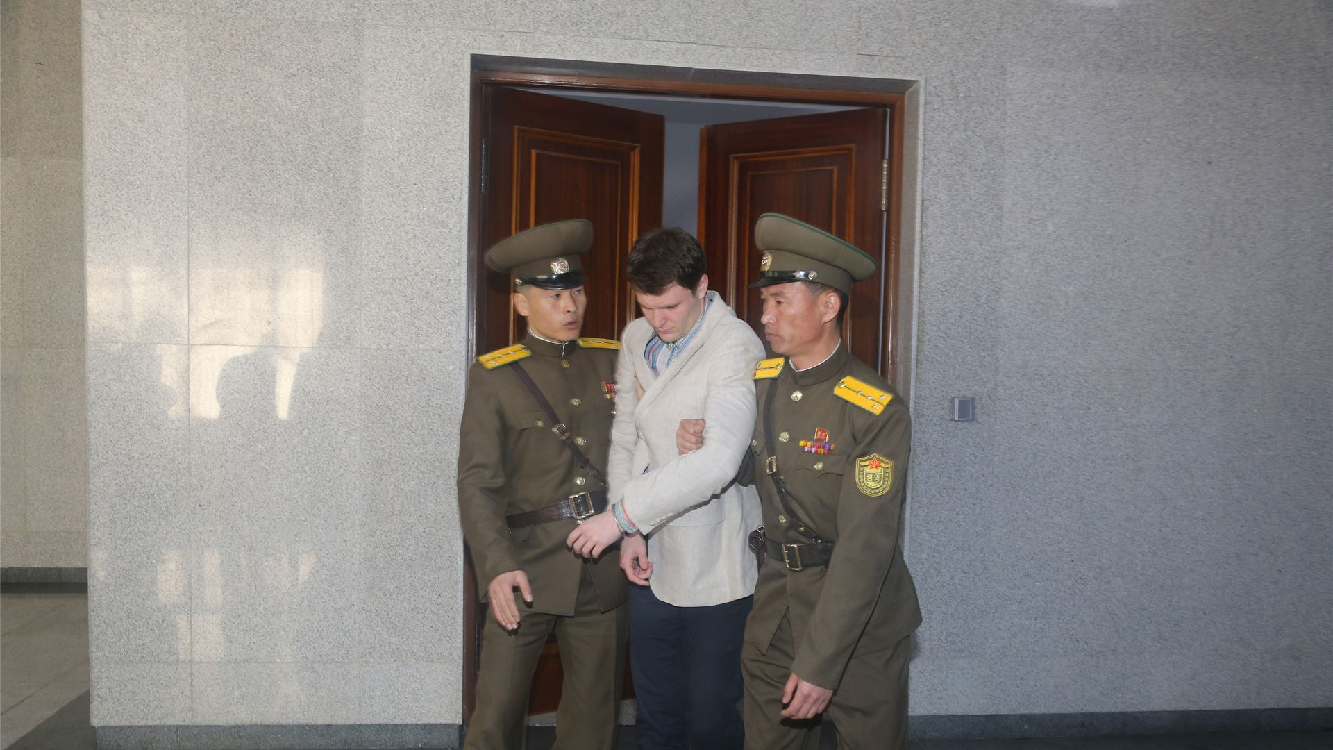 In this image, Otto Wambier is led through a doorway by two North Korean guards.