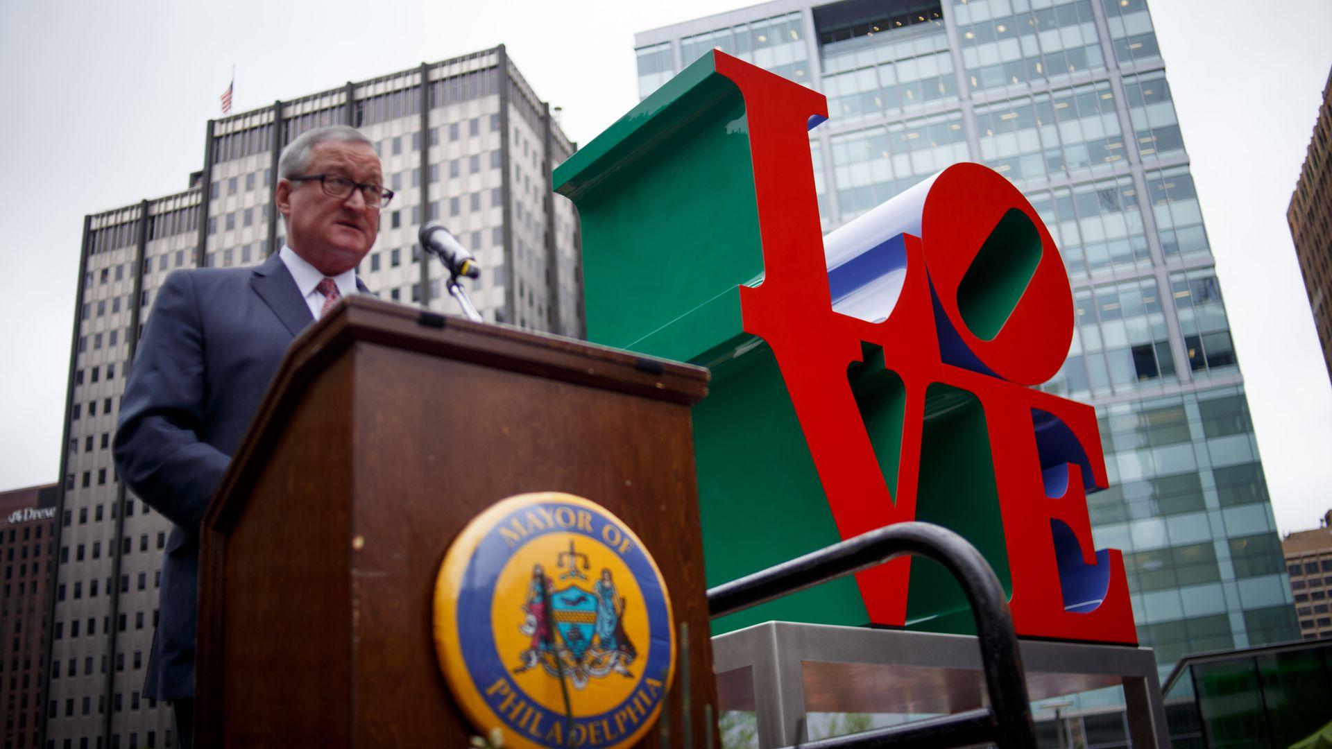 "The Philadelphia mayor speaks at a podium with the red sculpture of ""LOVE"" in the background"