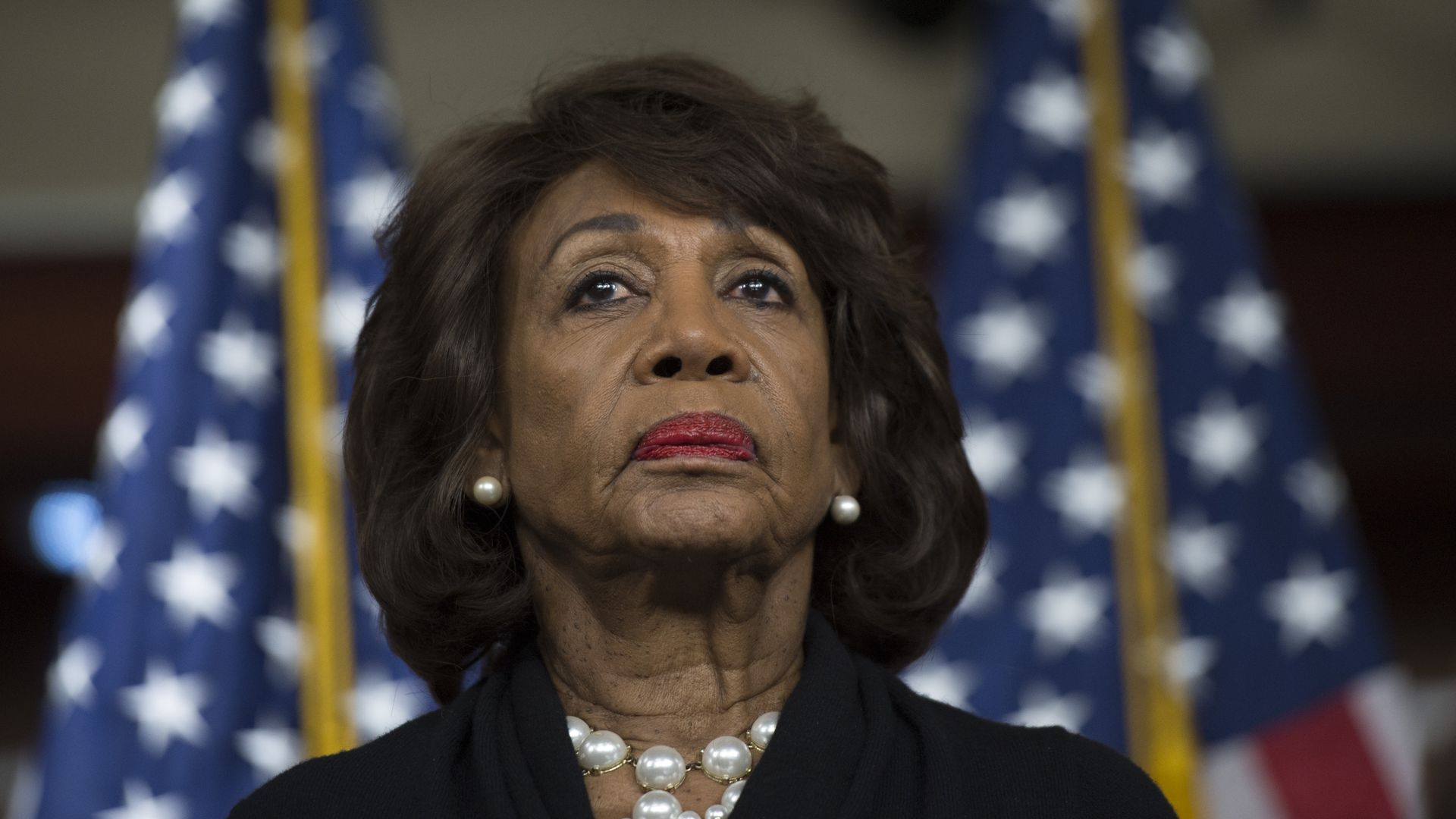 Maxine Waters in a black outfit frowning.