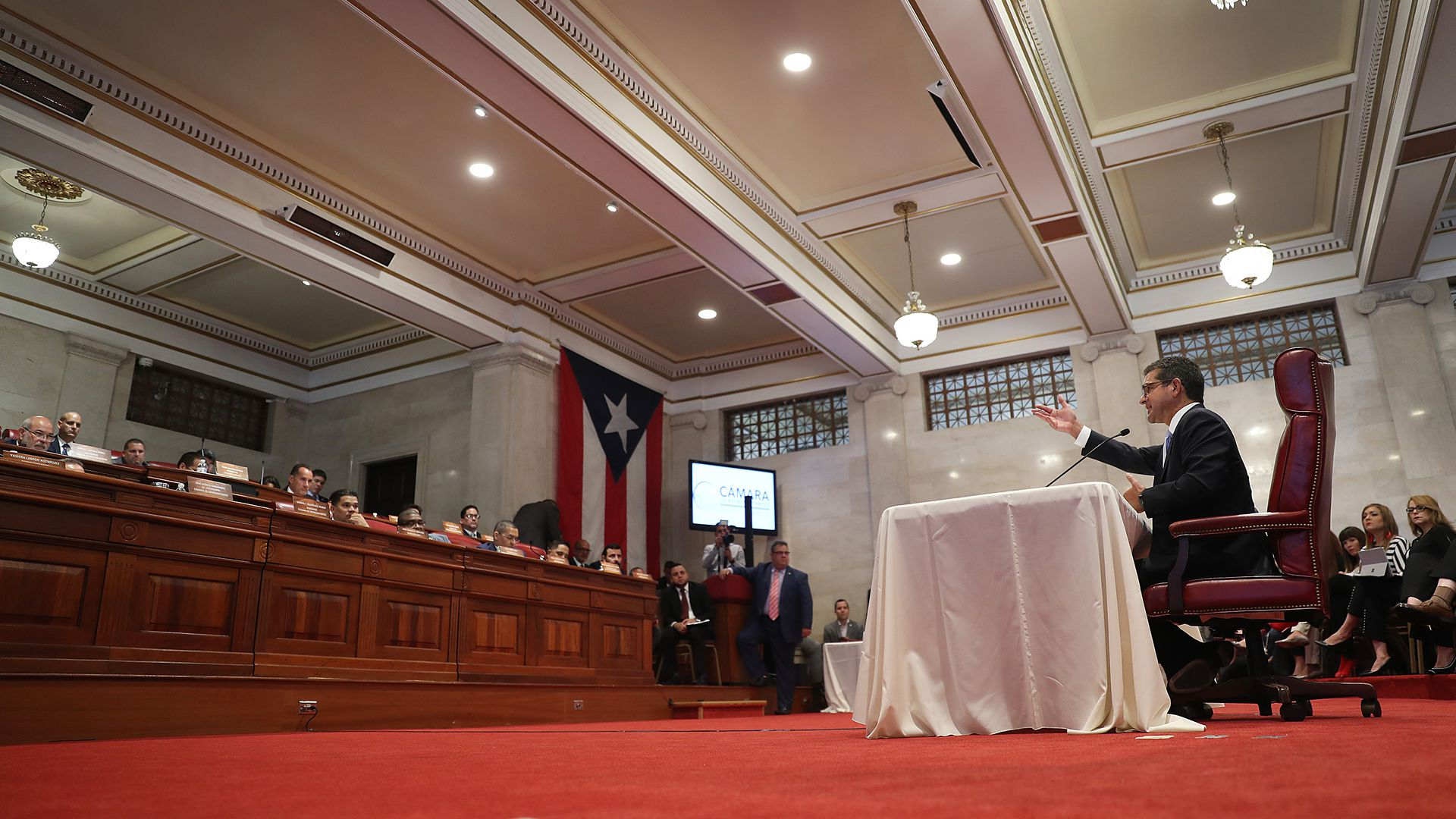In this image, Pedro sits in the Puerto Rican House of Representatives and speaks to a panel