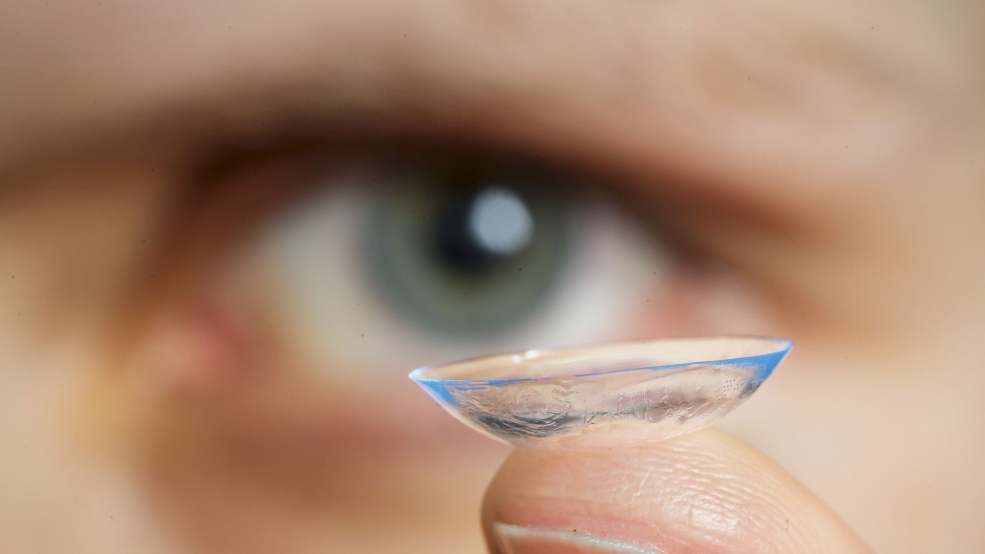 Someone holding up a contact lens on their finger with a blurred blue eye in the background