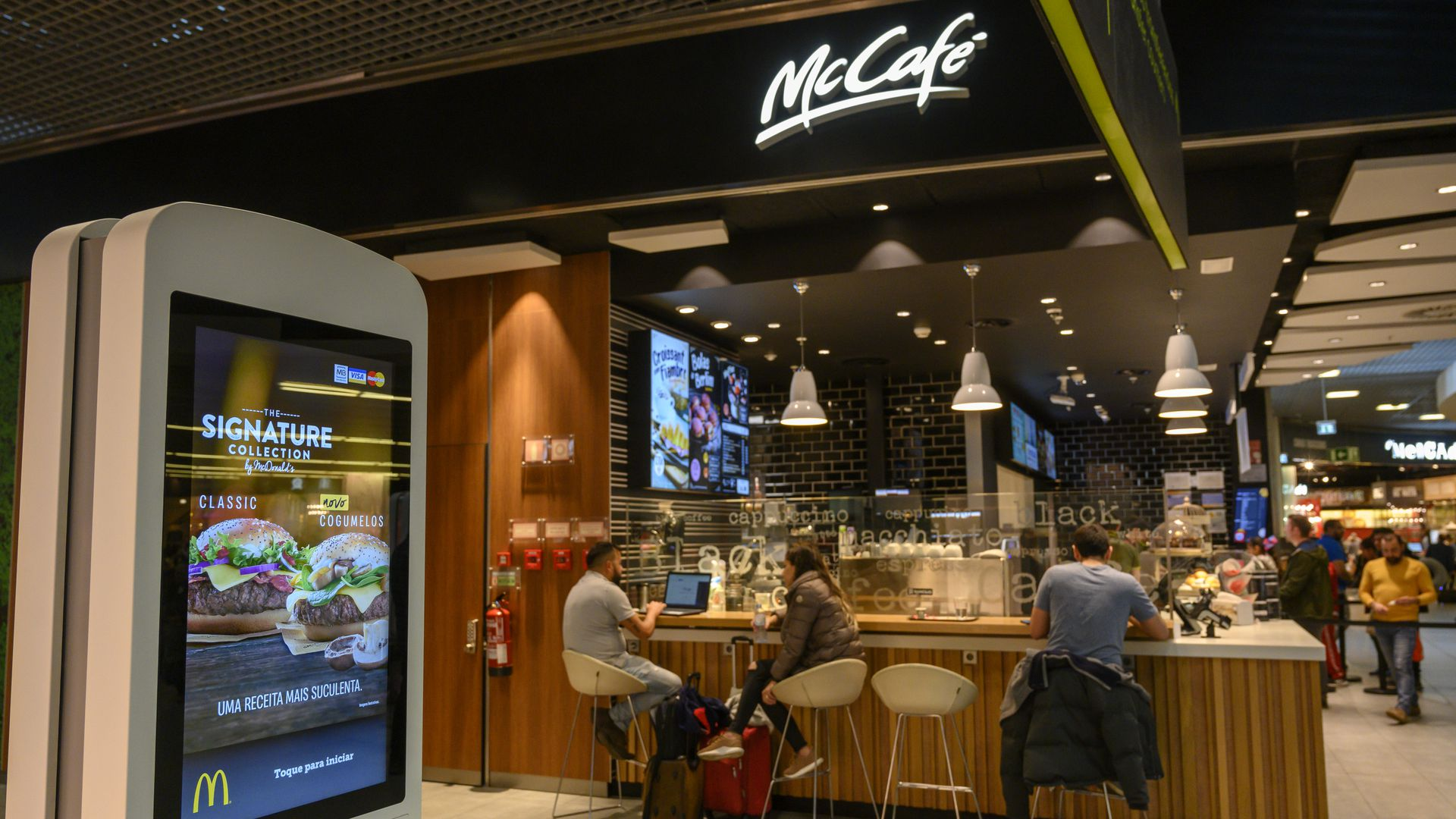 In this image, a man sits at a counter at a McCafe. In the foreground, a touch-screen stands upright for customers to order electronically.