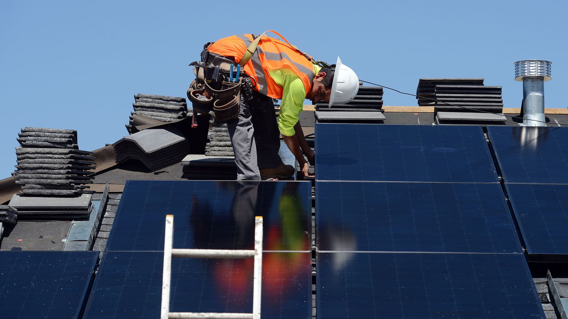 A worker installs solar panels on a roof
