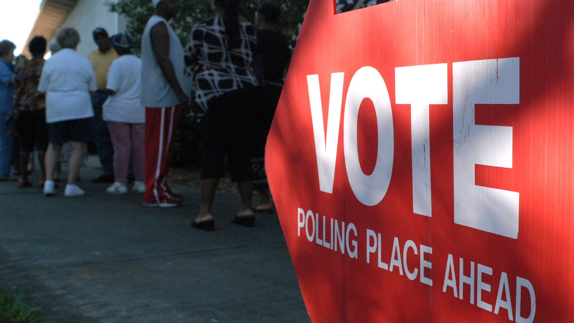 "A red arrow sign pointing left with the words ""vote polling place ahead"" in white lettering"