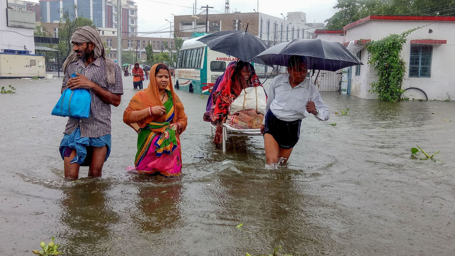 Patients wade through floodwaters on their way to hospital during heavy monsoon rain in Patna in the northeastern state of Bihar on September 28