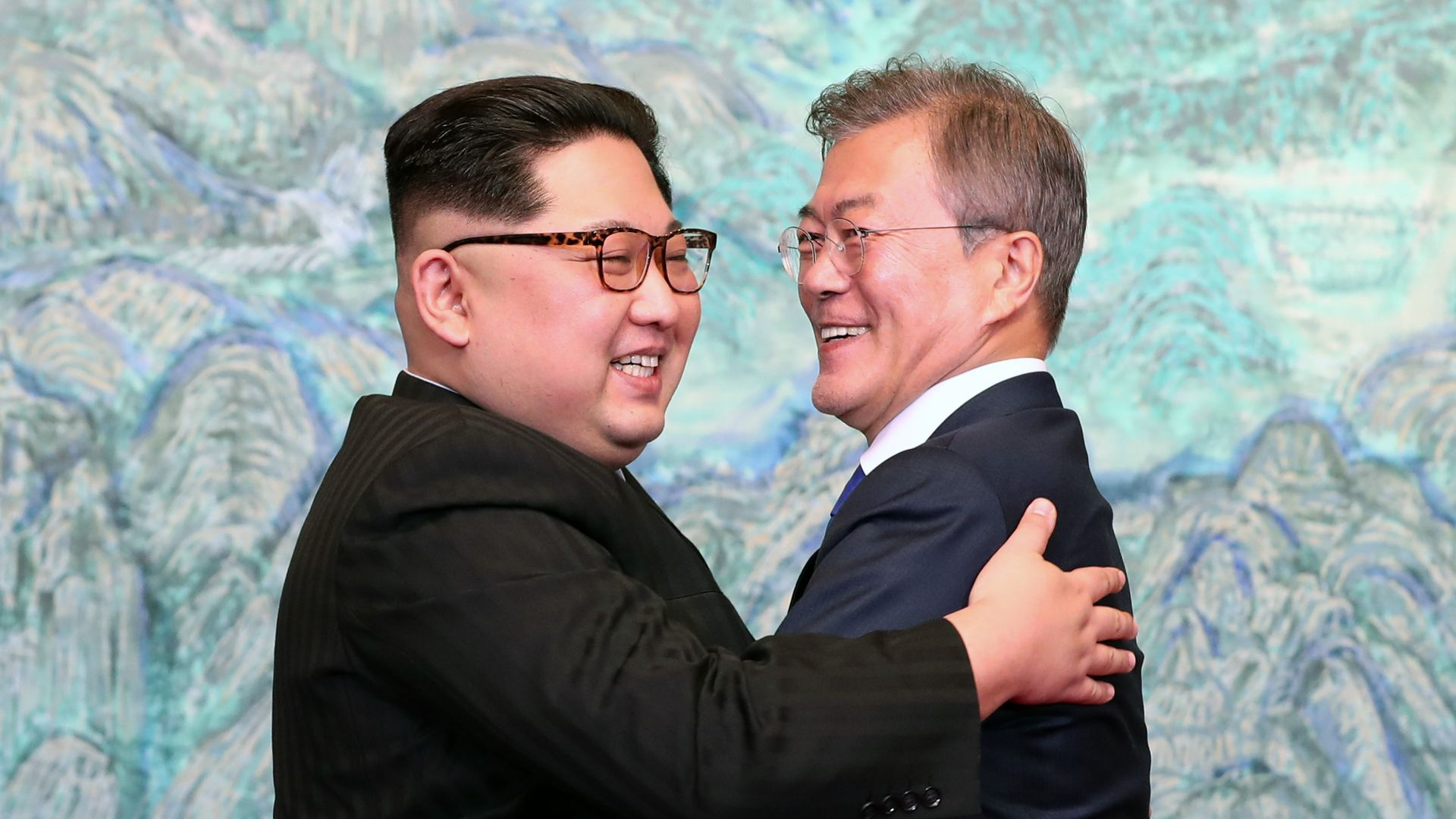Kim Jong-un ad Moon Jae-in embrace before a blue-green background.