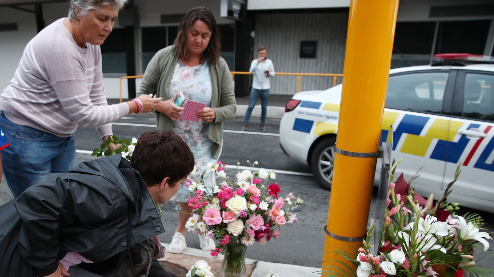 People dropping off flowers in solidarity with mosques in New Zealand.